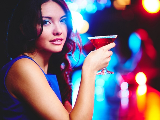 Pretty young girl with cocktail looking at camera on sparkling background