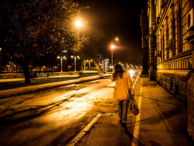 Young woman walking at city in night