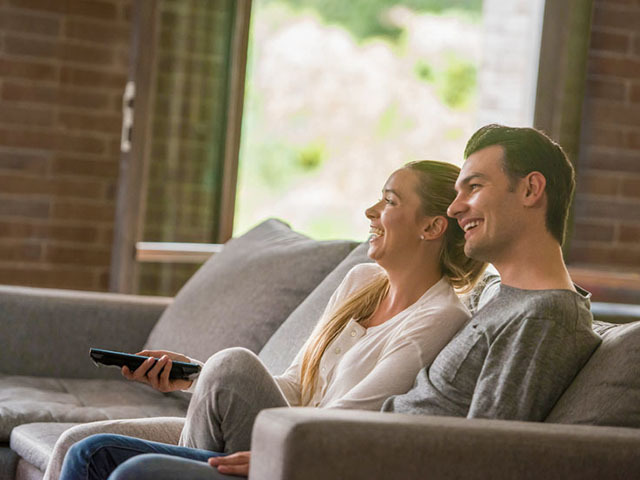 Happy couple relaxing at home and watching tv lying on the sofa and holding the remote control